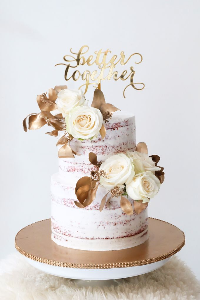 two tiered red velvet semi naked cake with white and gold theme