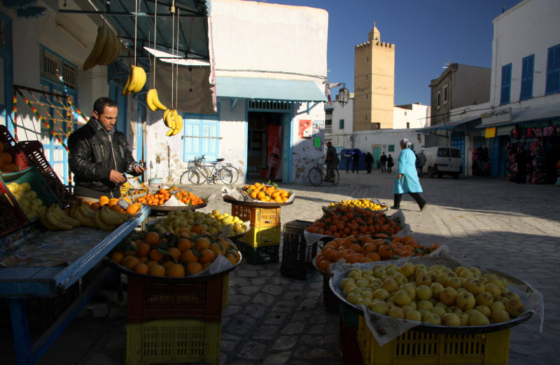 The grocers display early morning in the Medina The minaret of The Mosque of the Rose behind Kairouan Tunisia