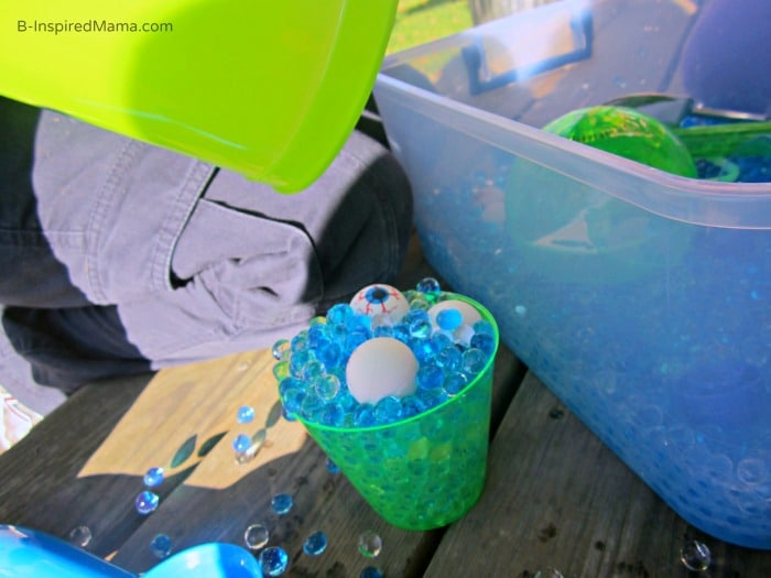 Scooping and Pouring During Our Monster Eyes Sensory Play at B-Inspired Mama