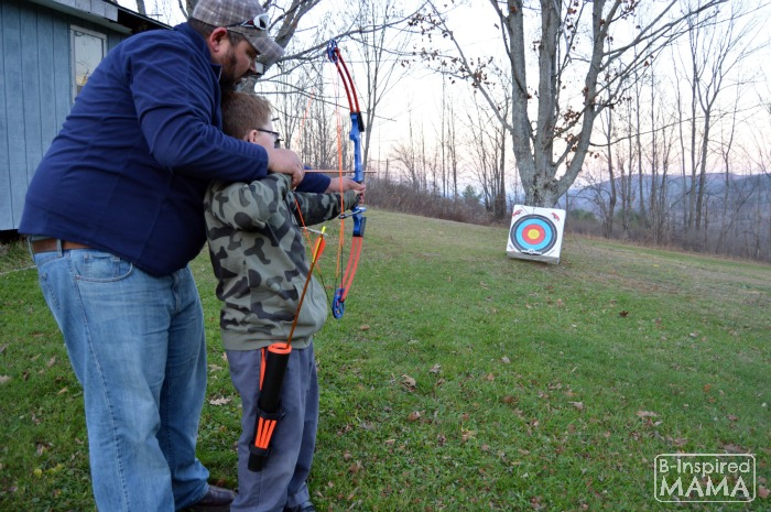 The Best Big Gifts for Kids - A 2015 Holiday Gift Guide - Cliff Helping Sawyer Shoot Bow - at B-Inspired Mama