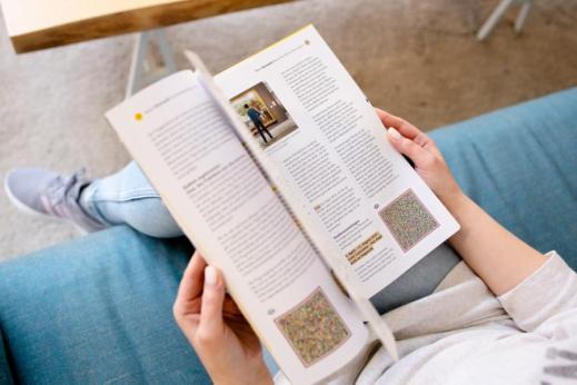 Eine Frau sitzt auf einem Sofa und hat ein aufgeklapptes Reisemagazin auf dem Schoß.