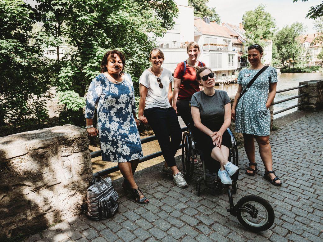 Auf dem Bild sind 5 Frauen zu sehen, davon eine junge Rollstuhlfahrerin. Sie posieren an einer Flusspromenade und ein großer Laubbaum wirft ein Schattenmuster auf sie. Es ist auf jeden Fall Sommer!