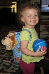 A cute little girl and her backpack.