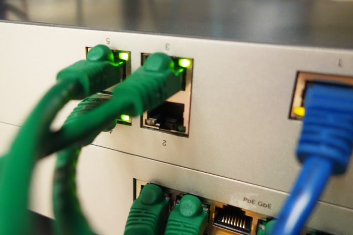 Green and blue ethernet cables plugged into a router