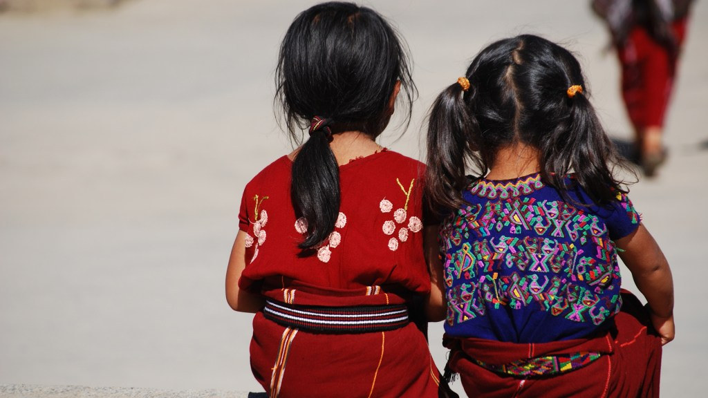 Young girls with dark hair, backs to camera