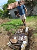David placing clay sculptures in the earth oven - Charokopio, Greece.