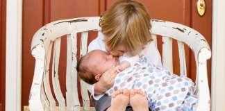 kisfiú ölében egy csecsemő és megpuszilja