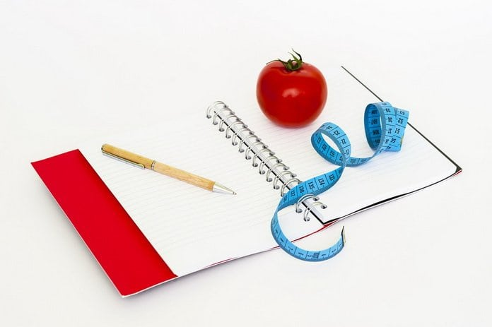 jegyzetfüzeten toll, mérőszalag és paradicsom