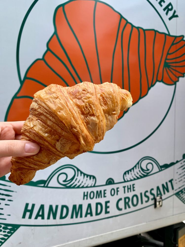 Fresh croissant in front of a cartoon croissant on the side of a delivery van