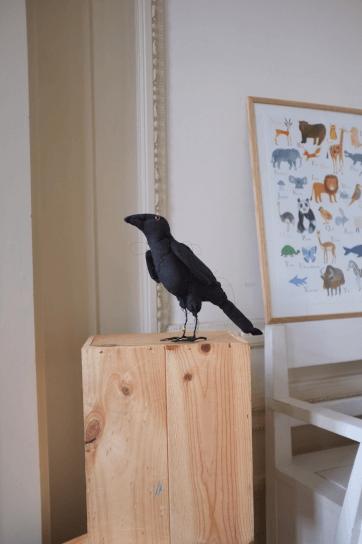 textiele vogel raaf op sokkel
