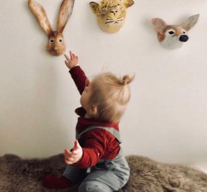 kindje op commode die hand uitsteekt naar papiermache haas die naast vo en panter hangt