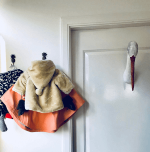 papiermache ooievaar op deur babykamer