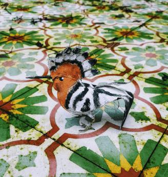 vogel van textiel oranje wit zwart op buitentafel