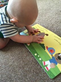 TM poking his finger through the star shaped hole in the open book on a page with dogs on it