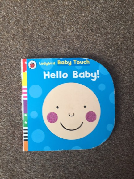 Cover of Hello Baby! book, cartoon baby's face on blue background