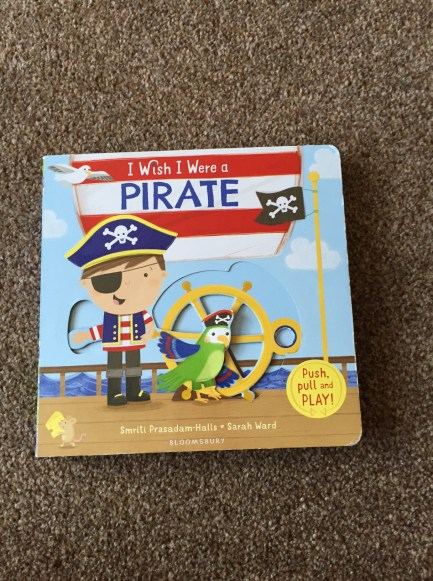 I wish I were a pirate book cover - a pirate and parrot on ship with a moveable helm
