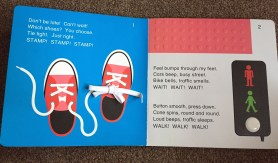 Open pages of the park book. One is a blue background with red sneakers on with actual laces. the other shoes traffic lights with a bumpy bit of page to show the pavement and a white button kids can press.