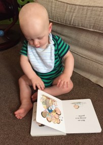 Bald 9 month old baby (wearing green vest with blue stripes and a pale blue stripy bib) sat on a beige carpet in front of a pale beige sofa reading an open book with illustration of a group of kids climbing over a dad