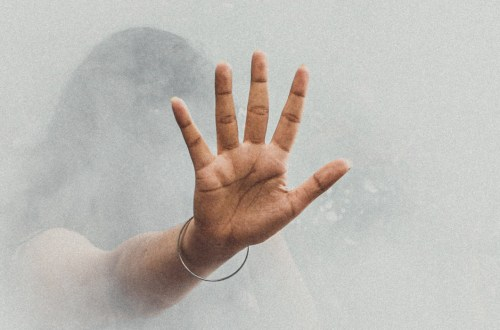 Ręka kobiety duszącej się oparami smogu