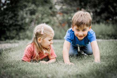 Le garçon est accroupi dans l'herbe