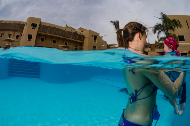 A woman in a bikini swims with a baby in a pool at a family holiday resort