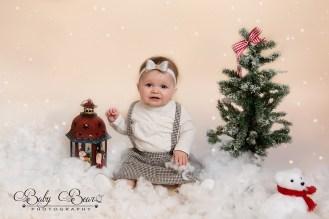Little girl sitting in snow for her Christmas shoot