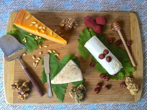 Cheese, fruit and nut board on fresh grape leaves