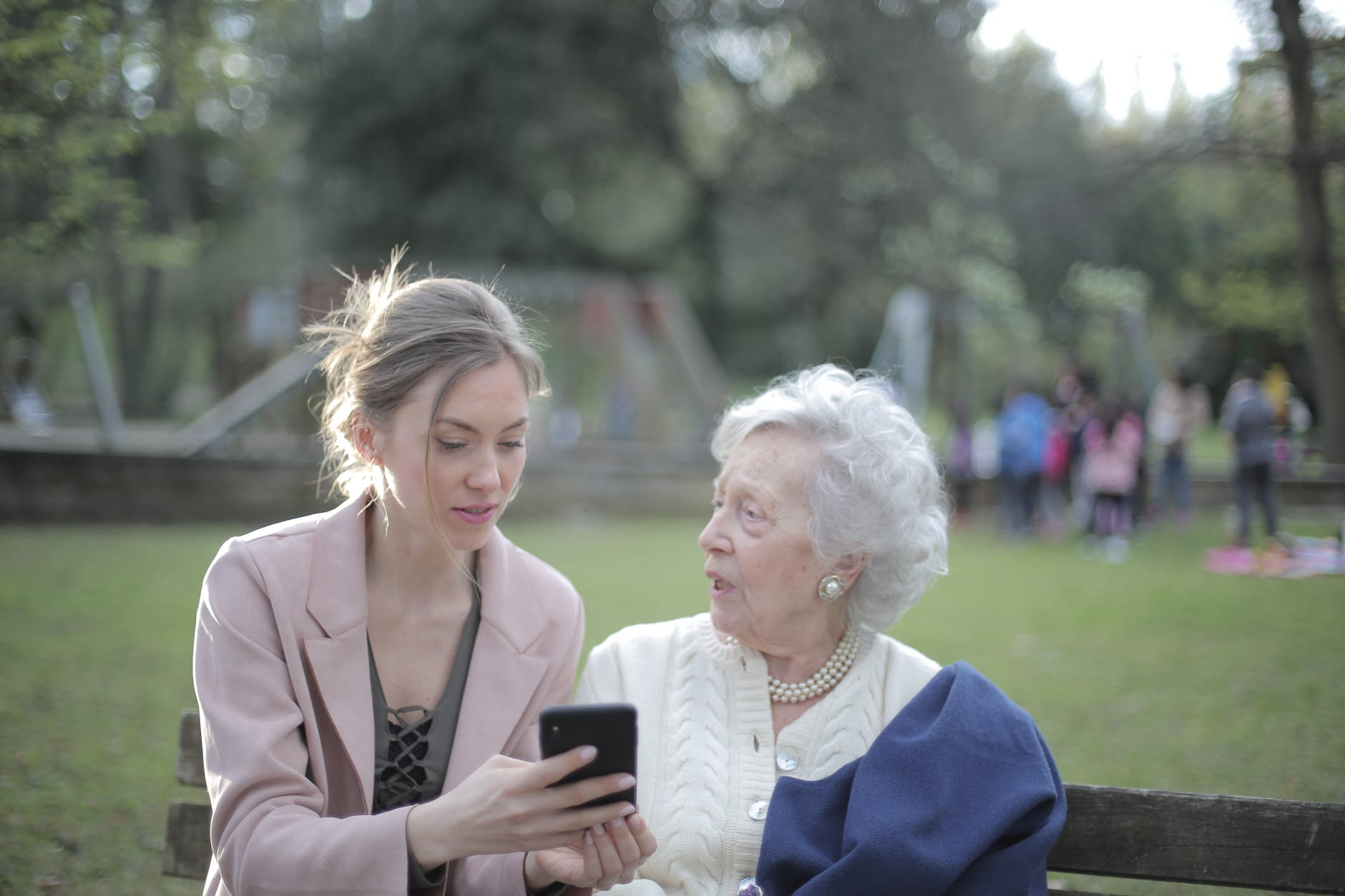 adult daughter teaching senior mother using smartphone in park
