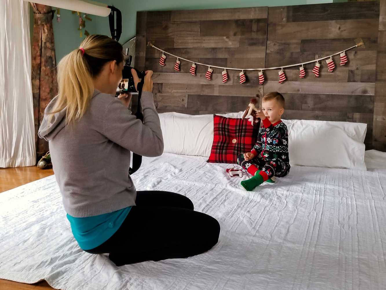 Holiday Photography Tips featured by top DC mommy blogger, Baby Castan on Board: professional photographer taking pictures of a toddler wearing Christmas pajamas