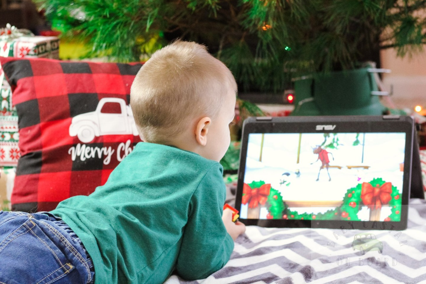 Best Christmas Movies for Toddlers featured by top Washington DC mommy blog, Baby Castan on Board: image of a toddler by a Christmas tree watching a Christmas movie