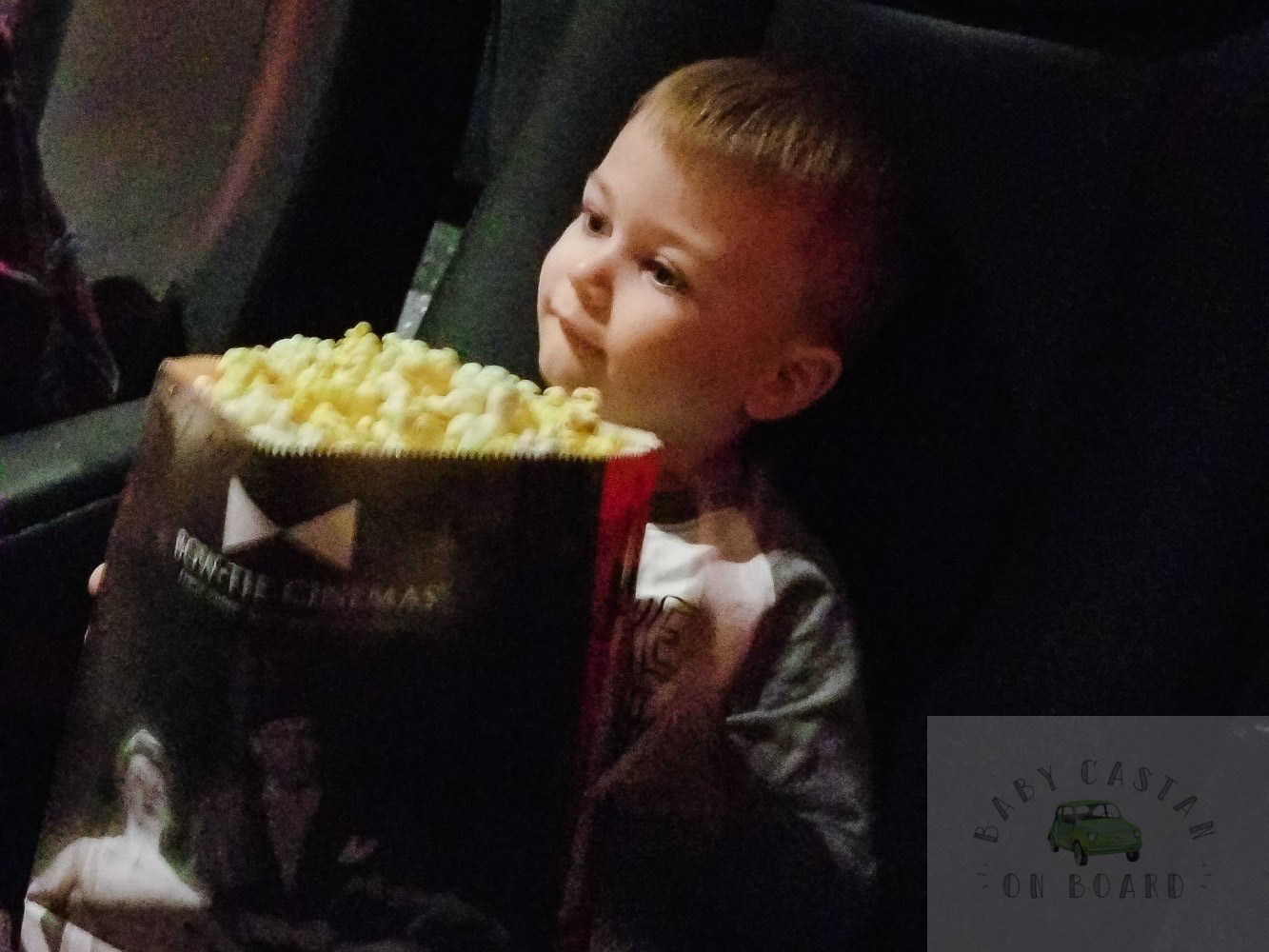 Tips for Taking Your Toddler to See The Grinch in Movie Theatres featured by top Washington DC mommy blog, Baby Castan on Board: image of a toddler eating popcorn at the theater
