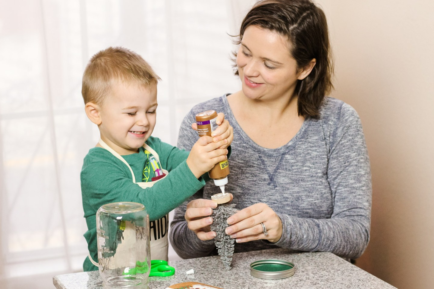 Easy Holiday crafts featured by top Washington DC mommy blog, Baby Castan on Board: image of a mom and toddler making a Christmas Tree Snow Globe craft together