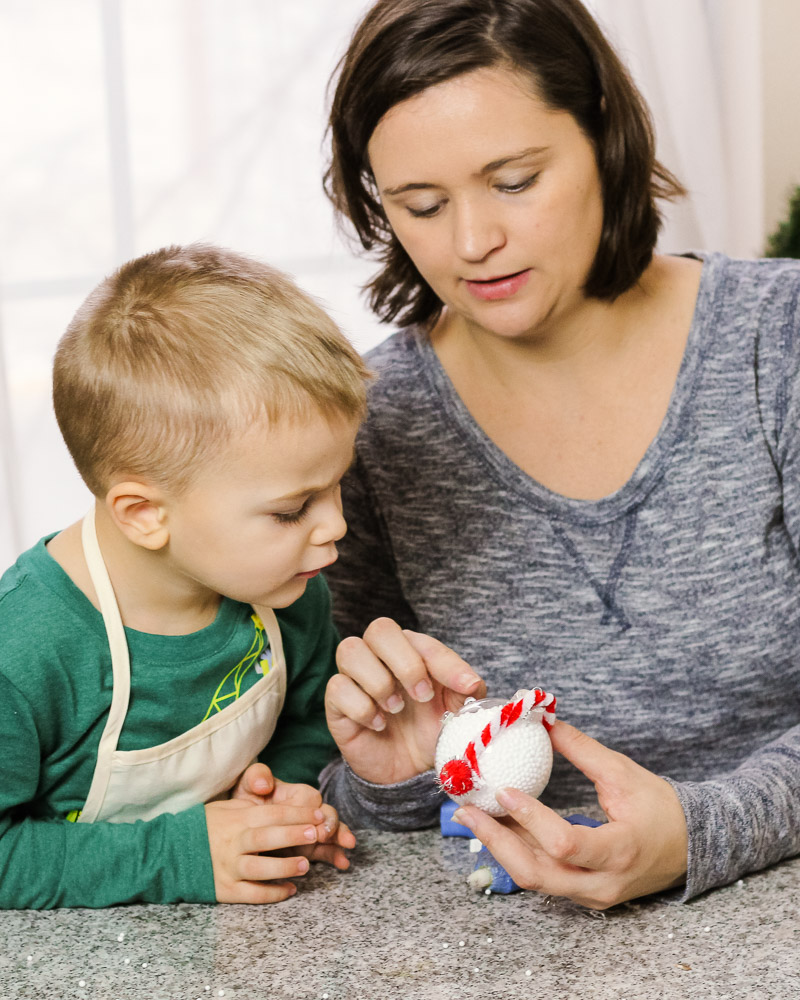 Toddler Christmas Ornaments_toddler helping mom glue googly eyes