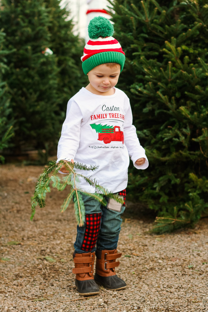 The Best toddler boy jeans featured by top DC mommy blog, Baby Castan on Board: image of a toddler boy wearing toddler boy jeans with patches, a Christmas graphic tshirt and pom striped beanie