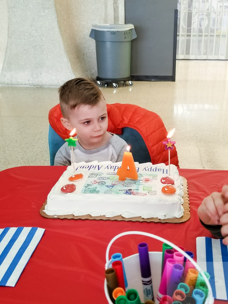 How to Plan a Birthday Party at the Airport for Your Child by popular DC mommy blog, Baby Castan on Board: image of a little boy sitting in front of a birthday cake with lit candles.