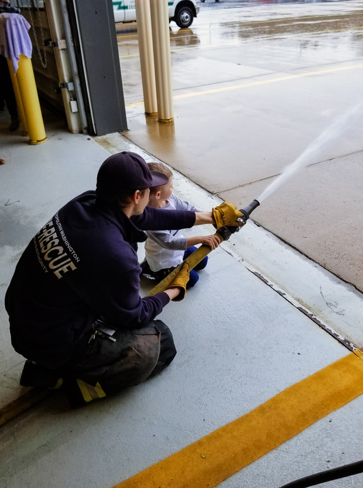 How to Plan a Birthday Party at the Airport for Your Child by popular DC mommy blog, Baby Castan on Board: image of a little boy helping spray water from a fire hose.