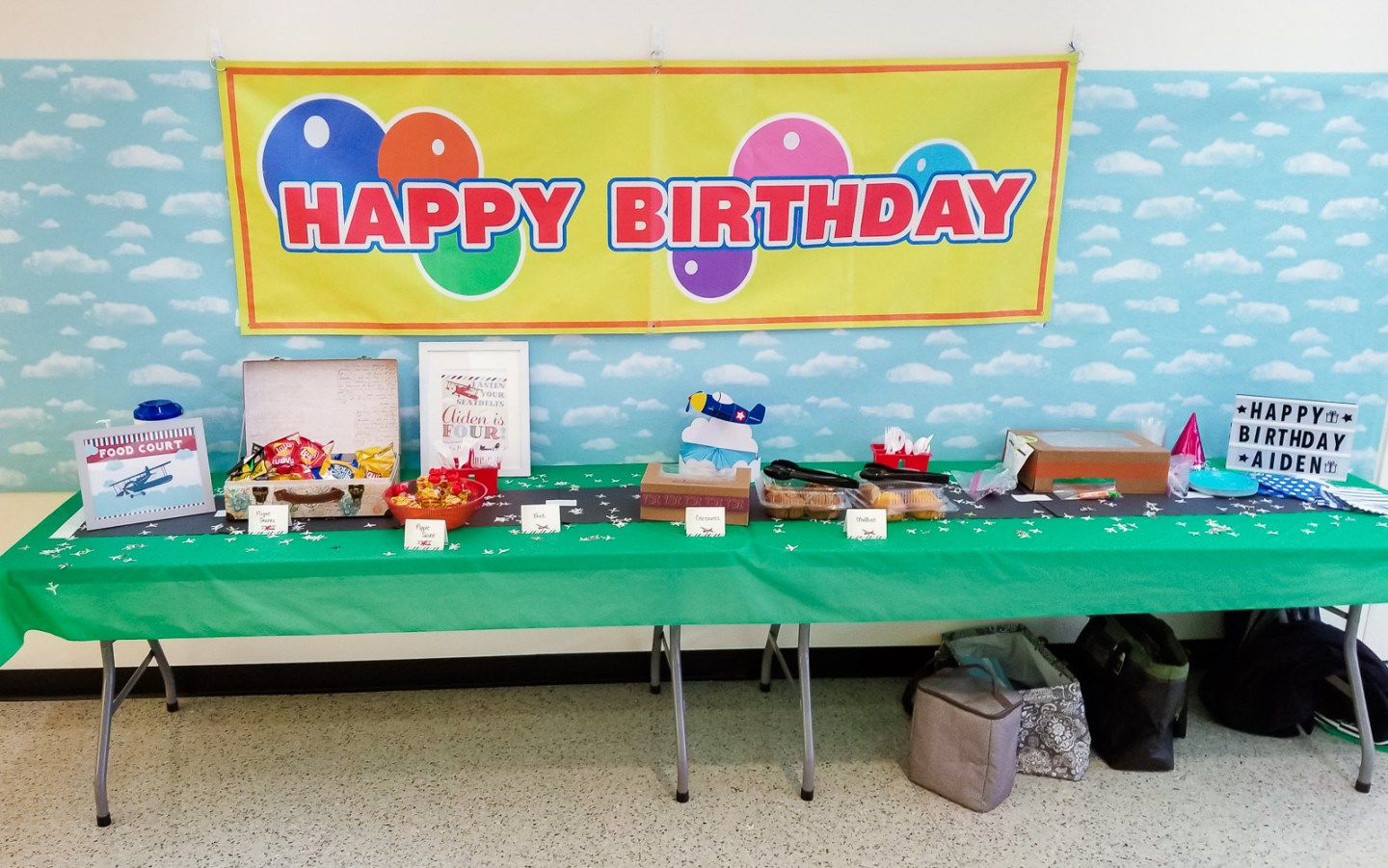 How to Plan a Birthday Party at the Airport for Your Child by popular DC mommy blog, Baby Castan on Board: image of a Happy Birthday banner hanging above two tables covered with green plastic tablecloths and containing muffins, cake, party hats, paper plates, and party favors.