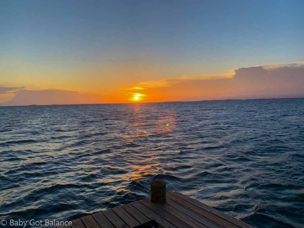 sun setting over the ocean, view from the dock of Coral Caye private island in Belize