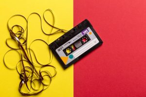black cassette tape on top of red and yellow surface 1626481