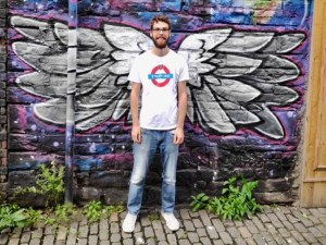 A man standing in front of a mural of angel wings.