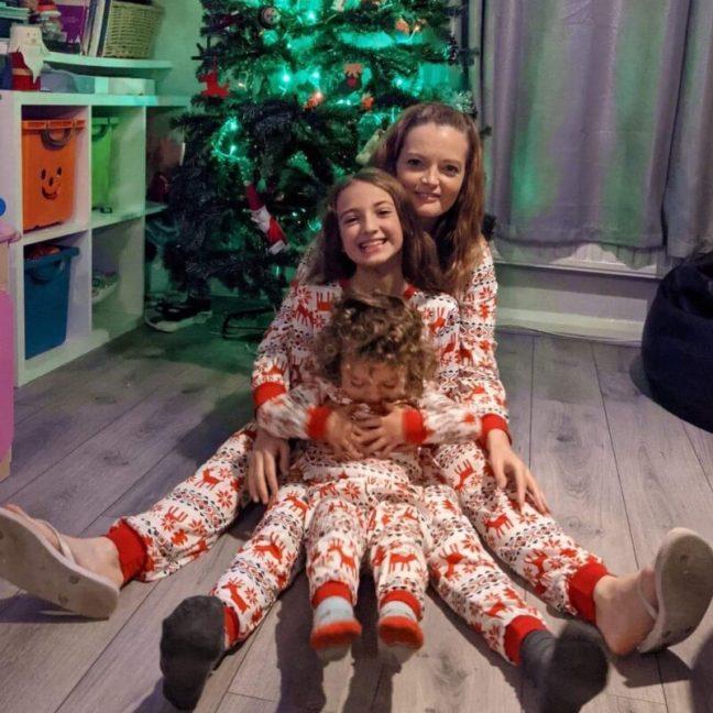 Mum and Kids in Matching Christmas Pyjamas on Christmas Eve