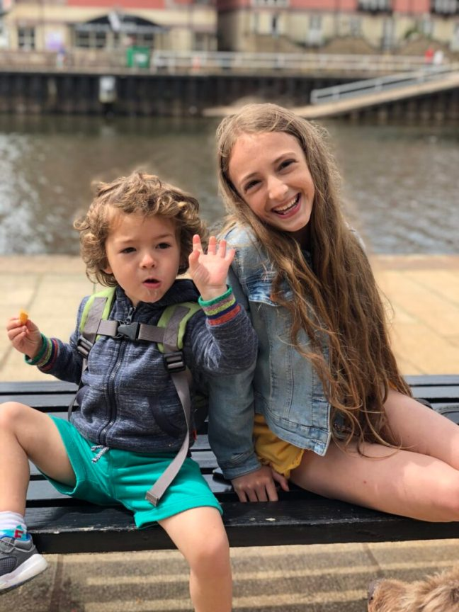 Toddler boy and ten year old girl sat on a bench at Exeter Quay