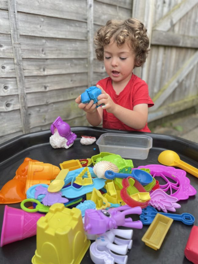 toddler boy playing with playdoh shapes and cutters