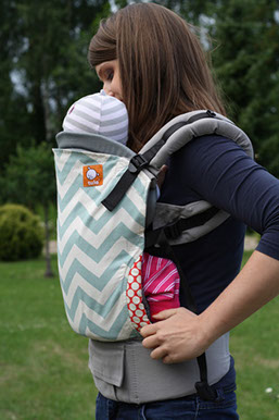 [Two photos side by side of a white woman with straight brown hair wearing a babylight teal and ecru chevron patterned buckle carrier with a gray newborn insert inside the carrier. The photo on the left she is looking down at the baby show is looking away from the camera. The photo on the right has the carrier not on the woman's shoulders to reveal the adorable baby looking at the camera inside the newborn insert with the woman's arms hugging the baby and smiling at the camera.]