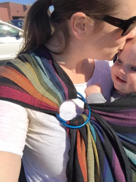 Image of a white woman kissing a smiling baby on the forehead. The baby is worn on her hip in a black and rainbow ring sling baby carrier with blue rings and a pleated shoulder. They are outside on a sunny day.