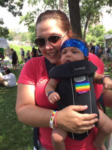 Image of a woman wearing sunglasses smiling as she wears a baby on her front facing out in a black soft-structured carrier designed for safe forward facing out. They are outside with lots of people behind them.
