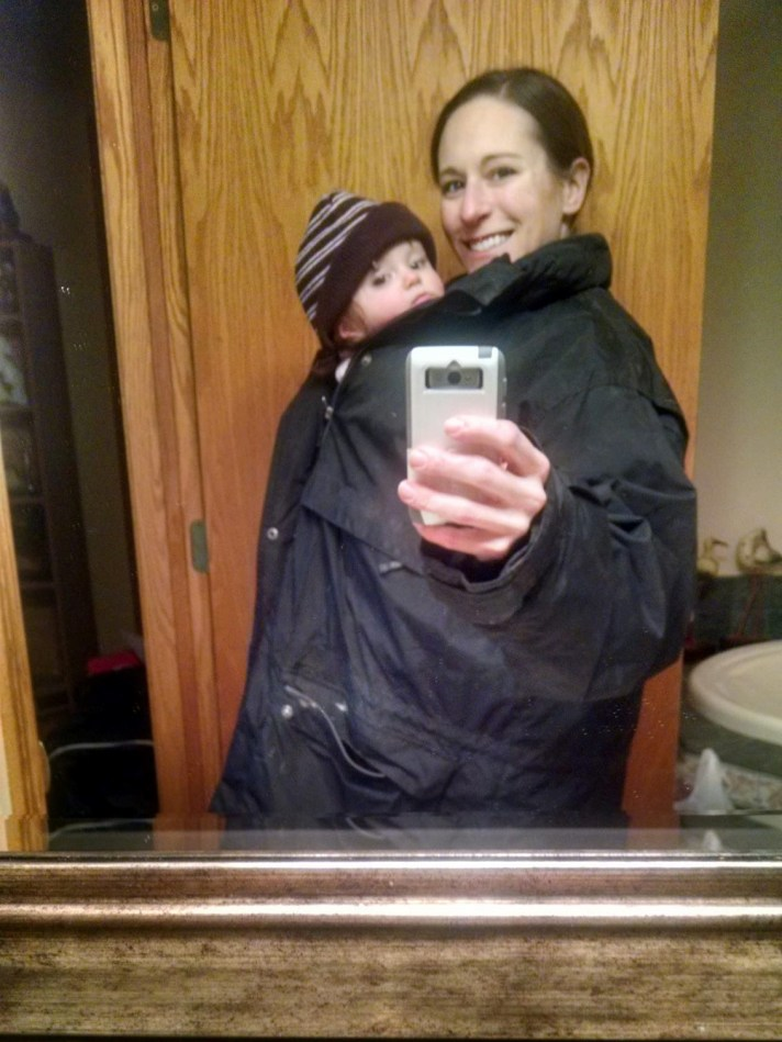 Image is a bathroom mirror selfie with a white woman and 9mo girl on her front sharing a black coat. The woman is smiling, the baby has a brown striped hat on and is not smiling.