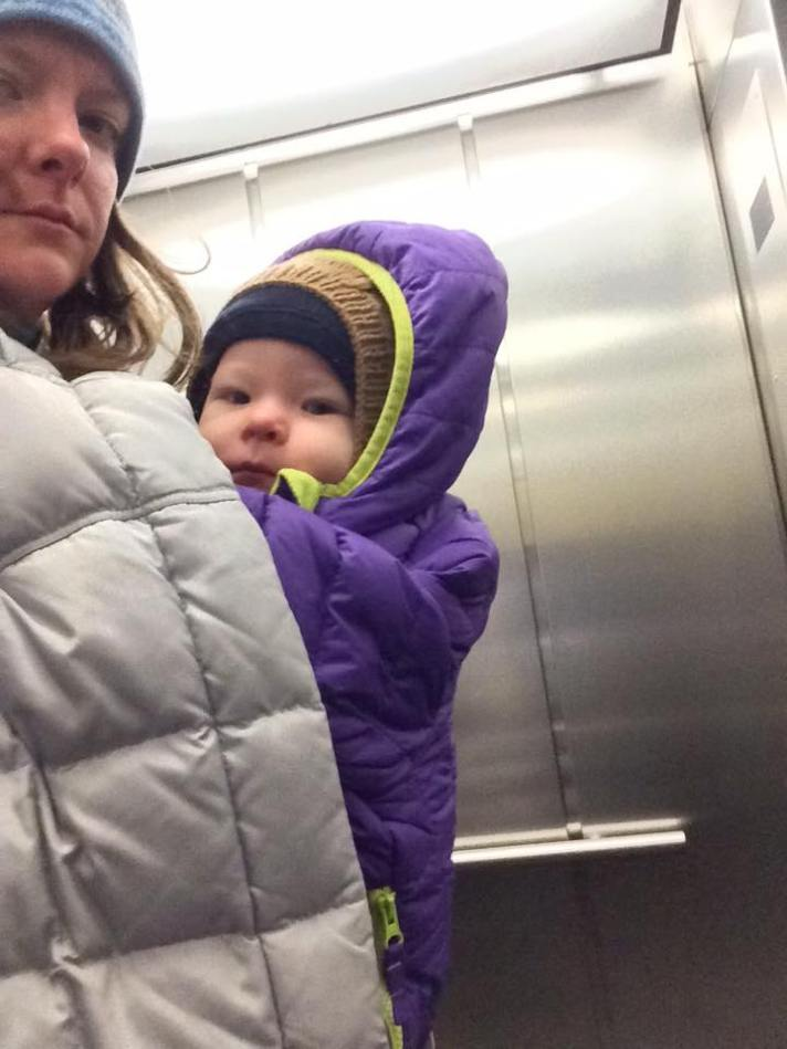 [image taken selfie style from the side of a white blonde woman wearing a gray coat and a white baby on her front. The baby is wearing a purple coat over the outside world of the carrier with its carrier threaded through the coat sleeves. ]