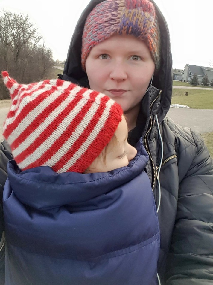 [Image: a white mother wearing a white-presenting child on her front. The child is wearing a red and white striped hat and is covered with a navy vest. The mother is wearing a jacket and a cold weather headband. They are outside.]