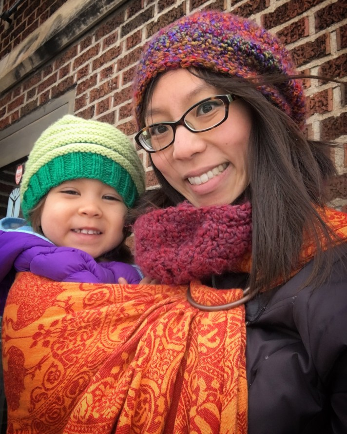 [Image of a smiling tan skin bespectacled Asian woman with dark brown hair wearing her smiling toddler on hip using a red and orange ring sling. They're both in Mama-made hats and wearing down coats. Behind them is a red brick wall.]